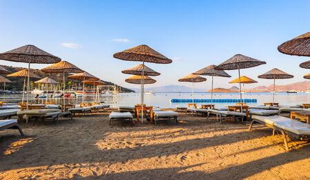 Beautiful beach on the shores of the calm blue bay of the Aegean Sea in the early morning. Beach vacation and holiday destination concept. Bitez, Bodrum, Turkey