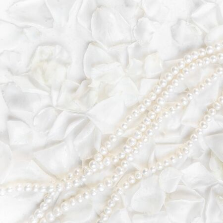 Pearl necklace on a background of white rose petals. Ideal for greeting cards for wedding, birthday, Valentines Day, Mothers Day