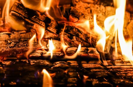 Flames of fire and hot coals of burned wood in the fireplace. Space for copy, text, your words. Horizontal