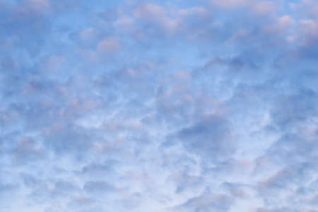 Blue sky background with white and pink clouds at sunset