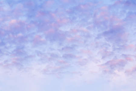 Background of blue sky with pale pink clouds in sunset