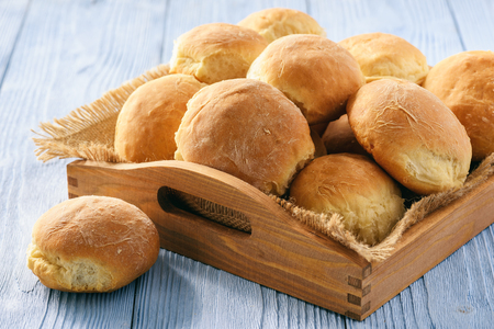 Homemade potato bread roll on wooden tray.