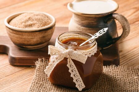 Caramel sauce on brown wooden background.