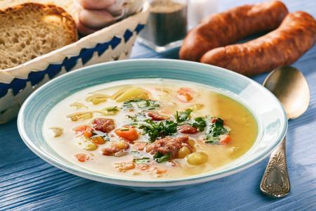 青い木製の背景にソーセージとエンドウ豆のスープ。 写真素材