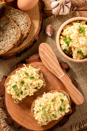 卵とチーズの全粒小麦のサンドイッチは、木の切り株に広がった。 写真素材