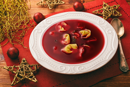 Traditional Polish christmas soup - red borscht soup with dumplings on white plate.