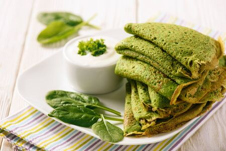 Spinach green pancakes (crepes) with sour cream.