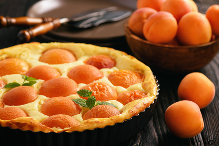 Homemade cheesecake with apricots on black wooden background. Stock Photo