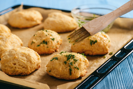 Homemade garlic cheese biscuits on a wooden background.