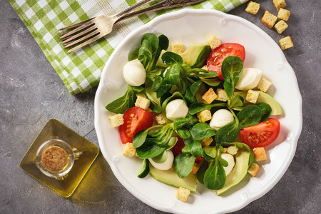 Salad with avocado, tomatoes, mozarrela and croutons. Stock Photo