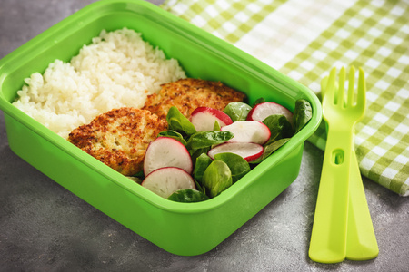 Lunch box with boiled rice, chicken cutlets ans radush salad. Stock Photo