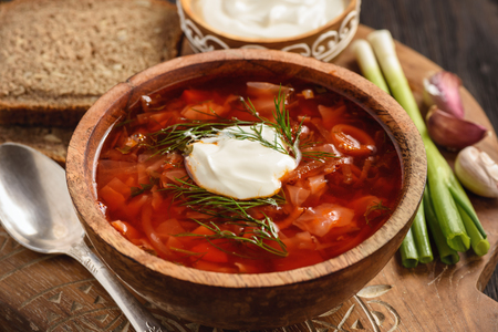 Borscht - traditional russian and ukrainian beetroot soup on wooden background.
