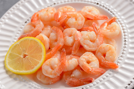 Cooked shrimps on a white plate with lemon.