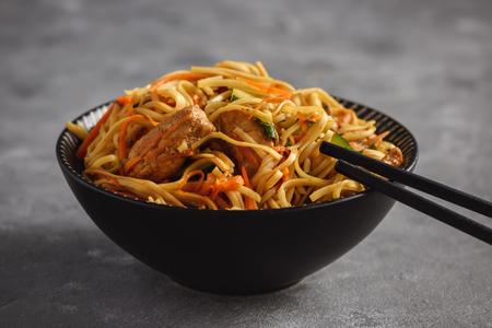 Nouilles asiatiques épicées avec poulet et légumes.