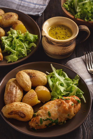 Chicken fillet baked with mozzarella and garlic butter. Served with roasted potatoes. 写真素材