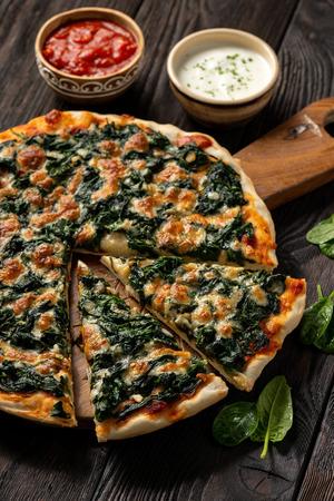 Homemade spinach pizza with mozzarella.