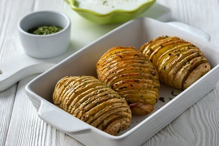 Hasselback potatoes baked with garlic and herbs in oven.
