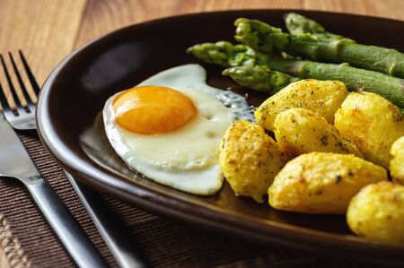 Grilled asparagus with fried egg and roasted potatoes. Stock Photo