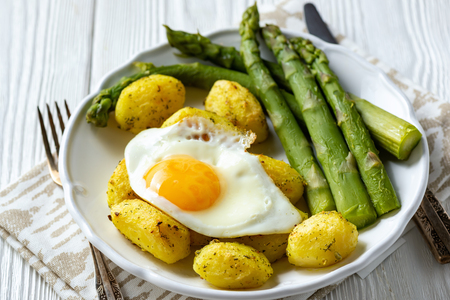 Grilled asparagus with fried egg and roasted potatoes. 写真素材