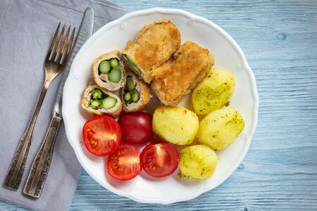 Roasted asparagus stuffed pork tenderloin served with potatoes and tomatoes. Stock Photo