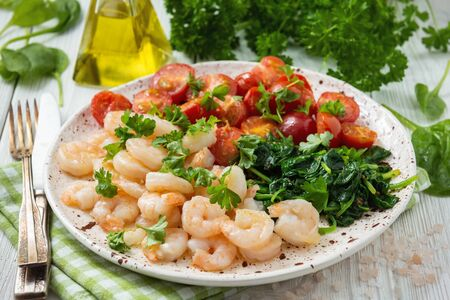 Grilled shrimps and tomatoes with spinach, garlic and parsley.