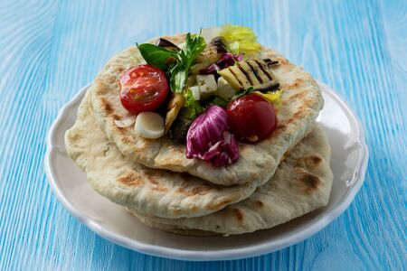Grilled eggplant, tomatoes and feta cheese salad with flatbread, mediterranean cuisine.