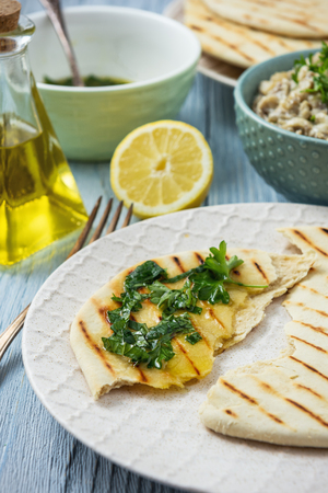 Pita bread with eggplant dip, olive oil and herbs, mediterranean cuisine.