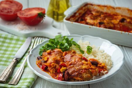 Chicken fillet baked in tomato sauce with corn and beans, served with boiled rice. Mexican style cuisine. Stock Photo