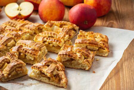 Homemade braided apple pie, on wooden background.