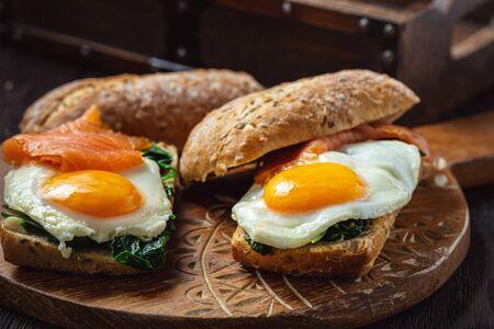 Panini con spinaci, salmone affumicato e uova che cola.