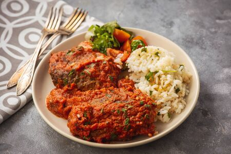 Minced meat cutlets in tomato sauce, served with rice, bifteki-greek cuisine.