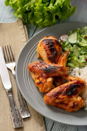 Grilled chicken wings and drumsticks, served with boiled rice and salad.