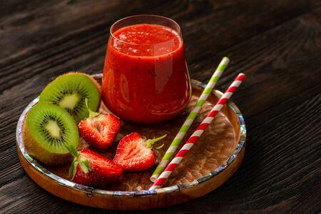 Strawberry and kiwi smoothie, on dark background.