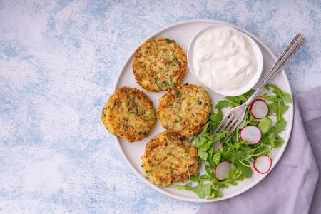 Zucchini fritters served with yogurt dip.