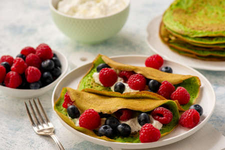 Spinach crepes with cheese, raspberries and blueberries. Stock Photo