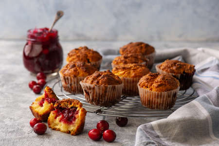 Homemade muffins with cranberry filling, on light background. Stock Photo