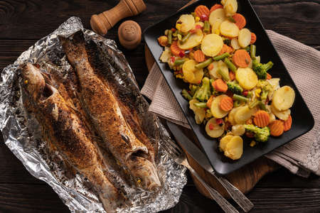 Homemade grilled labrax served with stewed vegetables. Stock Photo