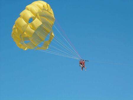 Couple paragliding against a bright blue sky.