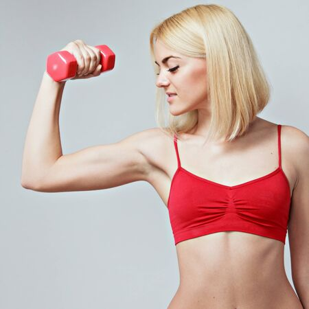 young fit woman lifting dumbbells on grey background photo