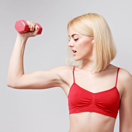 young woman working out with dumbbells on a grey background photo