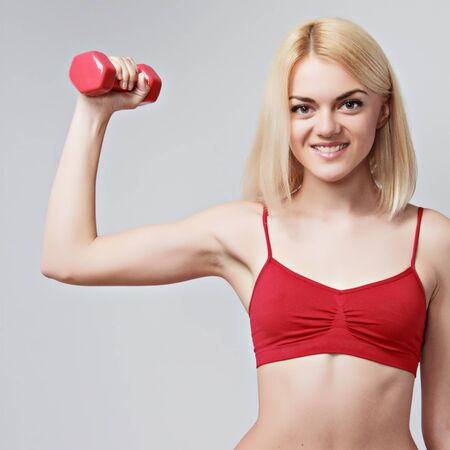 girl with a sports figure does exercises with dumbbells on grey background photo
