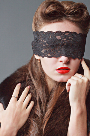 Portrait of a woman with a lace blindfold.