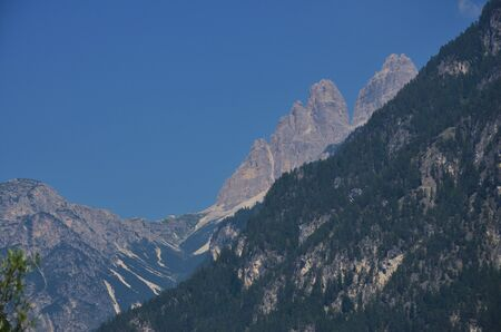 In a summer morning the peaks of Lavaredo stand out against the blue sky Фото со стока