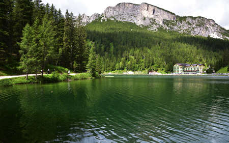 Walk on the path that runs along the lake of Misurina, in the green of the forests and with the background of the Col de Varda