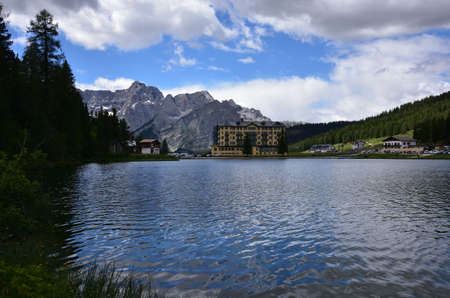 Summer on Lake Misurina, even on a cloudy day the blue of the sky is reflected in the waters of the lake