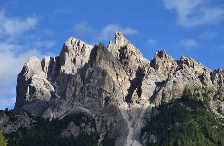 Part of the rocky peaks of Picco Vallandro illuminated by the last rays of the day