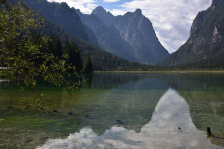 Mount Nasswand is reflected in the calms waters of Lake Dobbiaco Stock Photo