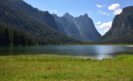 Quiet morning on Lake Dobbiaco surrounded by forests and high mountains