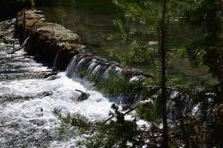 Small waterfall formed by the waters coming out of Lake Dobbiaco Stock Photo