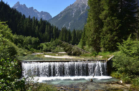A small leap of water into the stream that descends from the Fiscalina valley Stock Photo